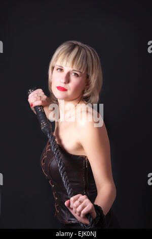 Woman on a black background with a whip in her hand - Stock Image