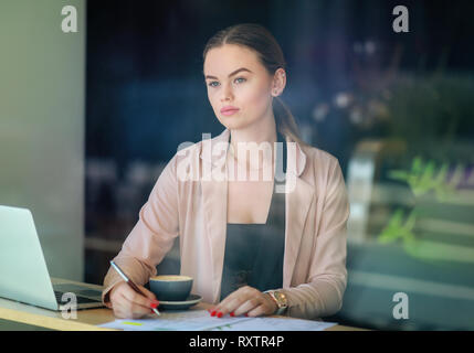 Elegant business woman looking through the window in a cafe shop. Thoughtful Look. Selective focus and reflexion on window - Stock Image