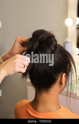Hair stylist hands fix high bunch of hair. Learning to create an evening hairstyle. Hairdressing workshop - Stock Image
