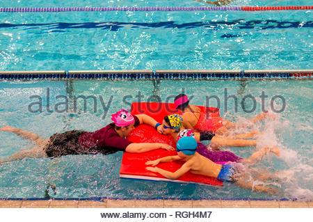 Poznan, Poland - January 26, 2019: Woman holding a mat with 4 children during swimming lesson in a pool in the Termy Maltanskie. - Stock Image