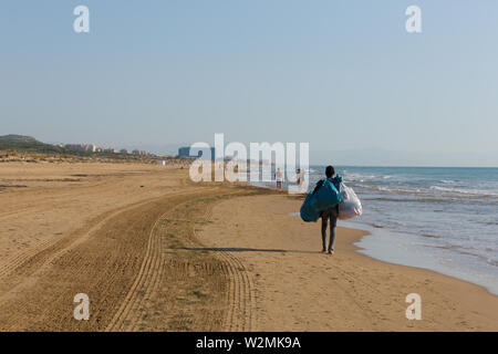 Black beach salesman walking with bags of goods to sell at Guardamar del Segura, Costa Blanca, Spain - Stock Image