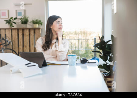 Young woman sitting at table at home looking sideways - Stock Image