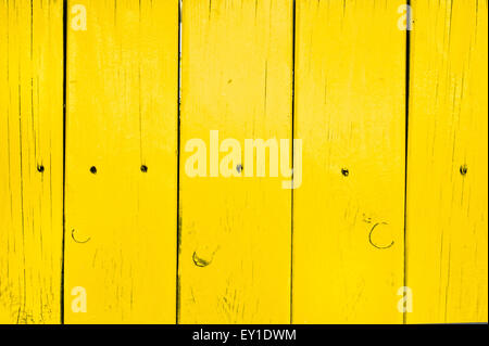 Part of a yellow painted fence as a background - Stock Image