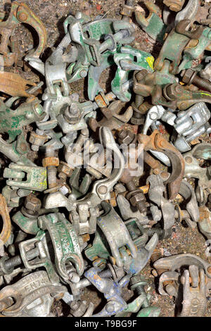 Pile of scaffolding double tube clamps on the ground used on a building site in UK - Stock Image