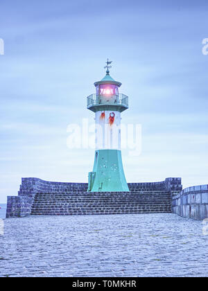 Shinning navigation lighthouse at pier end. Blue sunrise over Baltic Sea coast - Stock Image