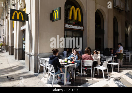McDonalds Spain - people sitting eating and drinking outside the McDonalds fast food restaurant, Malaga, Andalusia Spain Europe - Stock Image
