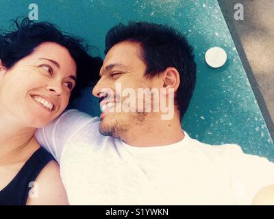 Lovers smiling at each other lying down outside - Stock Image