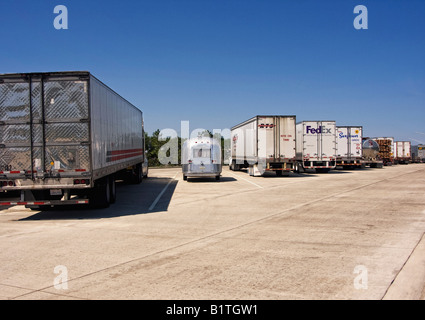 Vintage 1968 Airstream travel trailer parked between large trucks at a truck stop - Stock Image