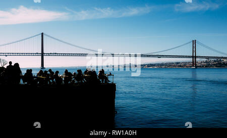 Silhouette of people relaxing in outdoor restaurant terrace overlooking the iconic 25 April bridge in Lisbon, Portugal, - Stock Image