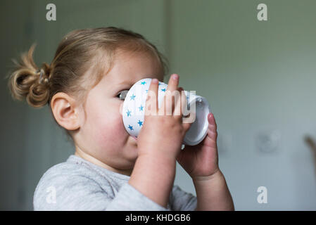 Little girl drinking from cup - Stock Image