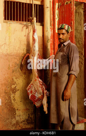A butcher with the remains of a cow,  Lahore, Pakistan, - Stock Image