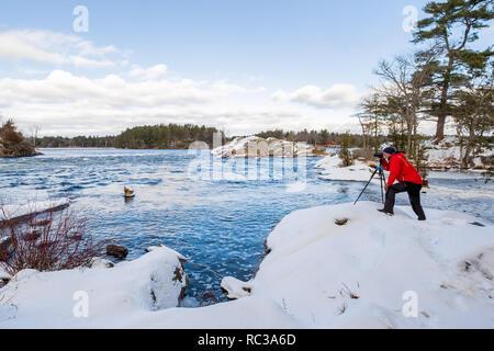 Photographer taking winter landscape shots at Burleigh Falls near Peterborough Ontario. - Stock Image