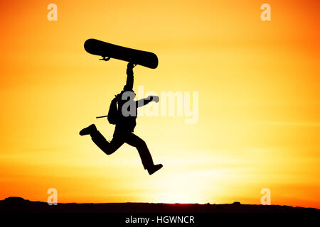 Happy snowboarder jump sunset ski - Stock Image