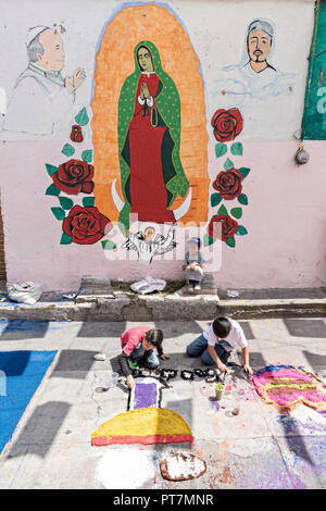 Young children create a floral carpet made from colored sawdust and decorated with flowers next to a mural of the Virgin of Guadalupe during the 8th Night Celebration marking the end of the Feast of St Michael in the central Mexican town of Uriangato, Guanajuato. Every year the town decorates 5km of road with religious icons in preparation for the statue of the patron saint to be paraded through the town. Uriangato became an international sensation after wowing Brussels with their floral carpet displayed at the Brussels Grand-Place during the Belgium Floral Carpet festival. - Stock Image
