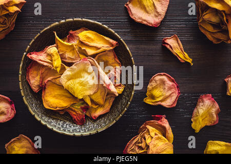 Brass Bowl of Dried Orange Rose Petals on Wood Table - Stock Image
