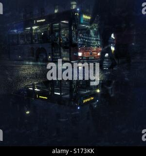 Bus reflected in a puddle after a rainshowe - Stock Image