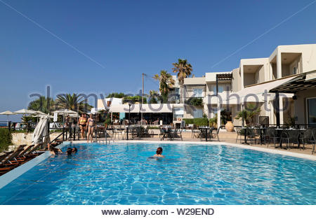 Chania, Crete, Greece. June 2019. A hotel swimming pool and holidaymakers overlooked by sea and pool facing accommodation units - Stock Image