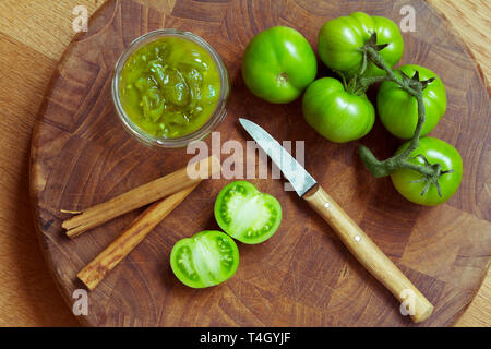 Jam or chutney in a glass jar made of green tomatoes with cinnamon, top view - Stock Image