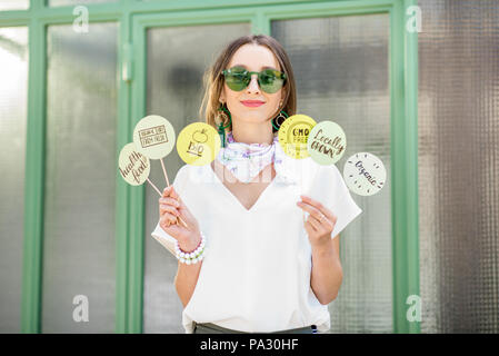 Young woman holding green plates with healthy eating slogans outdoors on the green background - Stock Image