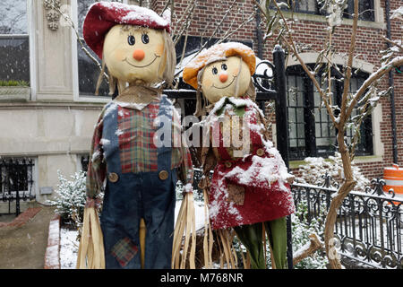 Urban scarecrow dolls covered in snow. - Stock Image