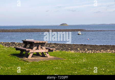 28 March 2018 A Mooring buoys on the sea at Killyleagh Northern Ireland with a small picnic table and council litter bin in the foreground. Green gras - Stock Image