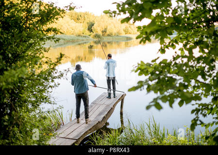 Two male friends fishing together standing on the wooden pier during the morning light on the beautiful lake - Stock Image