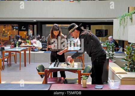 Man and woman in cafe at Galerias Lumière setting up a chess game on a table inside the restaurant in Porto, Portugal Europe EU  KATHY DEWITT - Stock Image