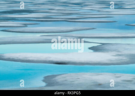 Pools of water amid the remaining ice on Smoke Lake reflects the sky on a spring evening, Algonquin Provincial Park, Ontario, Canada - Stock Image