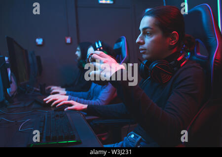 Pensive young programmer in black turtleneck sitting at table and drinking coffee from mug while working on software in dark room - Stock Image