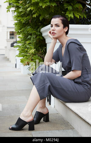 Chic woman in jumpsuit waiting on doorstep in London street - Stock Image