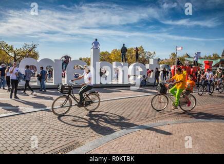 Riring a bike in Museumsplain near Iamsterdam sign - Stock Image