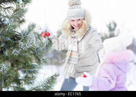 Happy mother and child playing with christmas tree decorations outdoor - Stock Image