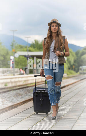 Young Woman Waiting On A Platform For Her Train - Stock Image