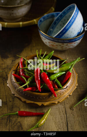 Thai red and green chilis or Prik chee fah also sometimes known as Birds Eye chile pepper fiery peppers rated at 50,000 to 100,000 scoville units - Stock Image