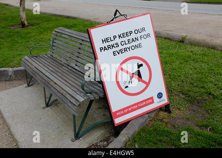 Sign in a Melbourne park requesting that dog owners pick up after their dogs - Stock Image