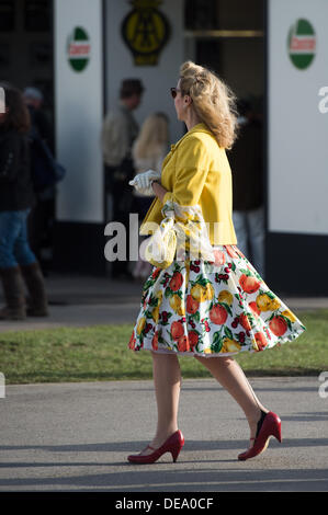 Chichester, West Sussex, UK. 14th Sep, 2013. Goodwood Revival. Goodwood Racing Circuit, West Sussex - Saturday 14th September. A visitor walks through the grounds dressed in period clothing - a floral dress, yellow jacket, seamed stockings and red shoes. Credit:  MeonStock/Alamy Live News - Stock Image