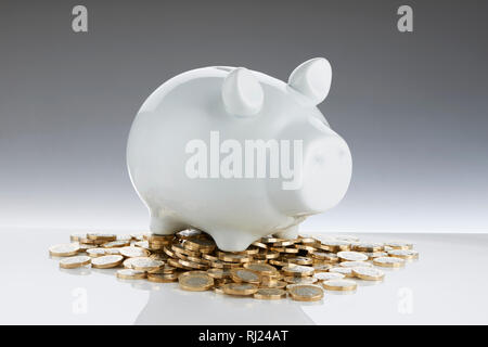 White Contemporary Piggy Bank with Pound Coins - Stock Image