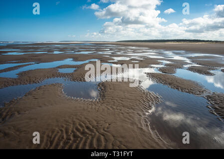 Patterns made by tide pools of water at low tide on Barnham Overy Staithe beach on Holkham bay, North Norfolk coast, East Anglia, England, UK. - Stock Image