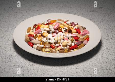 A round plate filled with mixed vitamin supplements- pills, tablets and capsules. - Stock Image