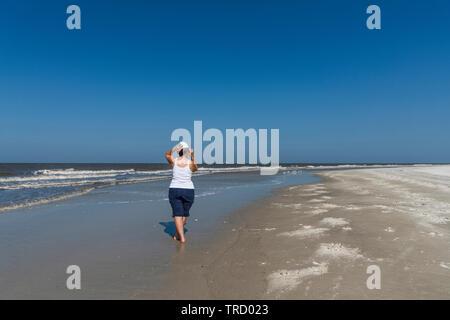 Girl walking the shoreline on Jekyll Island, Georgia USA - Stock Image