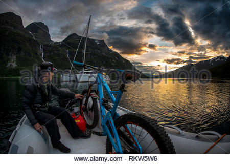 Man steers a dinghy with a mountain bike on board to the shore from a yacht on Lyngenfjord near the town of Birtavarre in Norway during the summer. - Stock Image