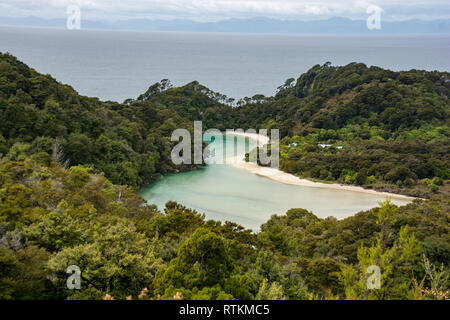 An inlet with blue water, white sand and forest in the Abel Tasman National Par, Nelson, New Zealand - Stock Image