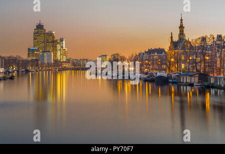 Amsterdam, Netherlands,  along the river Amstel with office buildings (Rembrandttoren/Mondriaantoren) and houses/façades in golden morning light. - Stock Image
