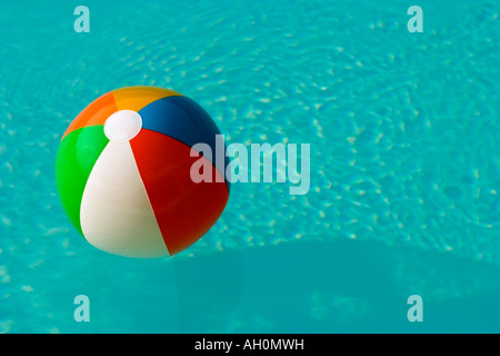 Colourful beach ball floating in a swimming pool with bright blue water - Stock Image