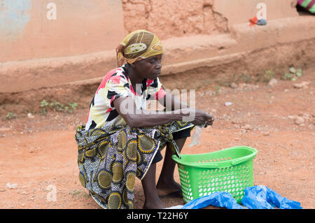 Adzopé, côte d'ivoire - June 10, 2017: woman seated on a stool, head tied by a scarf, before her an empty basket and a bag in hand - Stock Image
