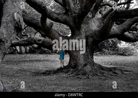 Girl looking our from behind very old big tree(oak). Black and White photo with girl in color, Goose Island, Texas - Stock Image