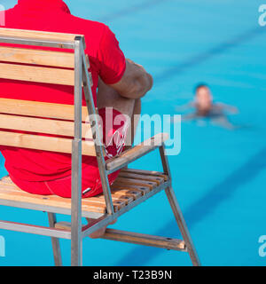 Lifeguard on duty, sitting in chair above swimming pool. - Stock Image
