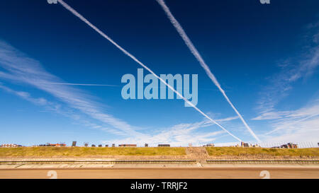Aircraft vapour trails cross a brilliant blue summer sky above Blackpool Beach and the Blackpool Illuminations tableaux of Bispham Cliffs. - Stock Image