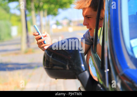 France, teenager playing Pokemon Go. - Stock Image