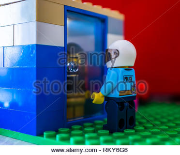 Poznan, Poland - February 10, 2019: Lego policeman with helmet standing in front of a door waiting until man opens in soft focus. - Stock Image